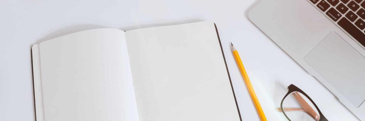 Notizblock, Stift und Laptop