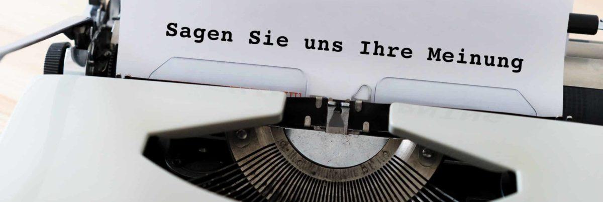 """Schreibmaschine mit Text auf Blatt """"Sagen Sie uns Ihre Meinung"""""""